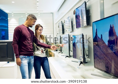 Couple in shopping. They are looking for new tv. They are pointing fingers at tv. Shallow depth of field.