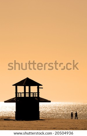 Couple in silhouette walking along sunny beach at sunset with dark watch tower