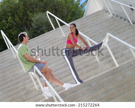 Couple, in sportswear, warming down from jog, man leaning against railing on steps, woman stretching leg (tilt)