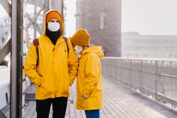 Couple in surgical face masks dressed in yellow jackets, confused because of the coronavirus are standing on the bridge. Girl is buried with concern in her boyfriends shoulder. Covid-19 concept.