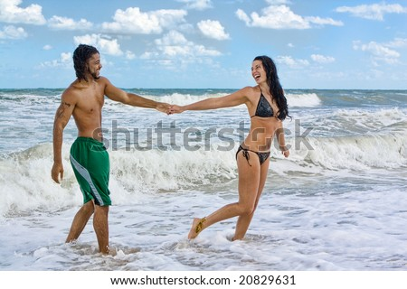 Couple in swim suits standing at the beach