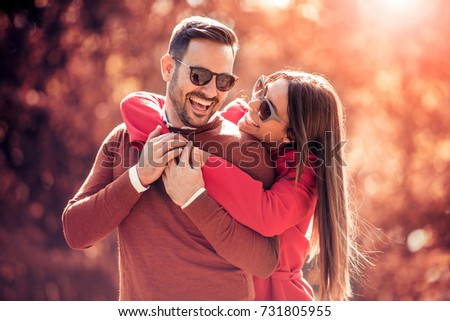Couple in the autumn park.Smiling man and woman outside.