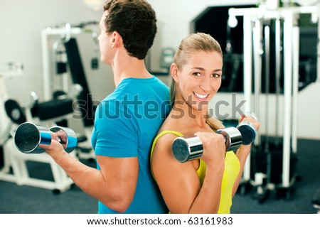 couple in the gym, rivaling each other, exercising with dumbbells (focus on the faces)