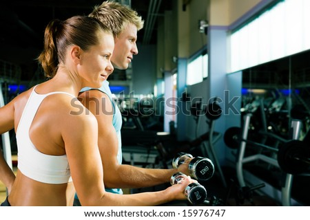 couple in the gym, rivaling each other, exercising with weights (focus on the face of the girl)