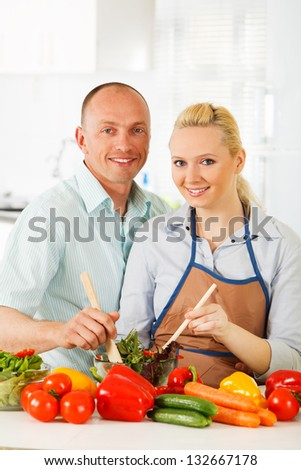 Couple in the kitchen with vegetables.