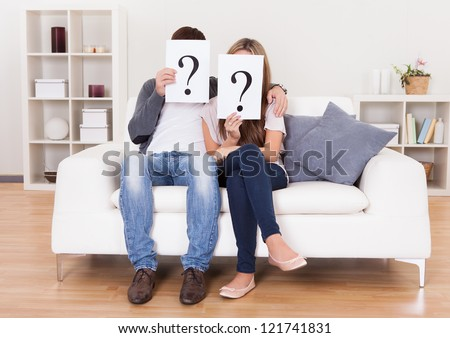 Couple in the living room with question marks in front of their faces