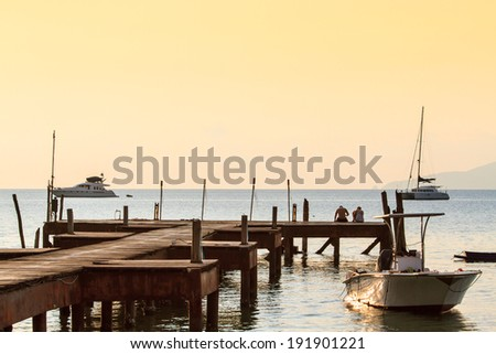 Couple in the sunset time sitting at wooden bridge on the way to the harbor in Sunset time at Mak island, thailand