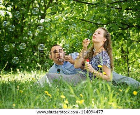 Couple in the woods blow bubbles