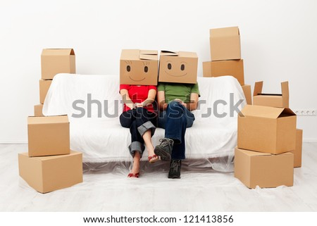 Couple in their new home with cardboard boxes, sitting on covered sofa