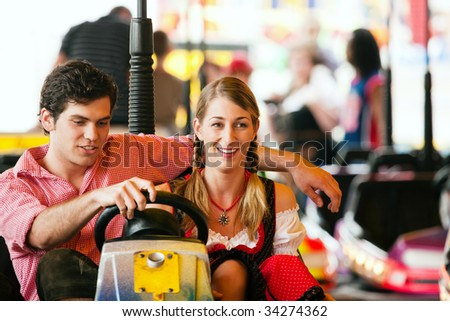 Couple in traditional German or Bavarian costume in a bumper car / dodgem ride - stock photo