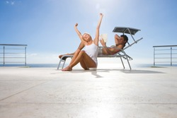 Couple in underwear stretching and reading book on balcony lounger