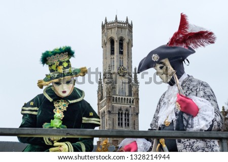 Couple in Venetian carnival costumes, wearing masks, in front of a gothic tower in the centre of Bruges #1328214944