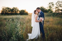 couple in wedding attire with a bouquet of flowers and greenery is in the hands against the backdrop of the field at sunset, the bride and groom