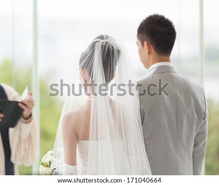 Couple in white wedding ceremony