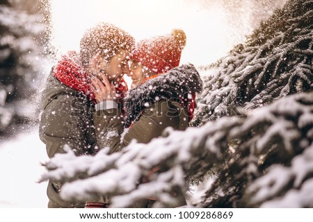 Stock Photo Couple in winter by the fir tree under falling snow