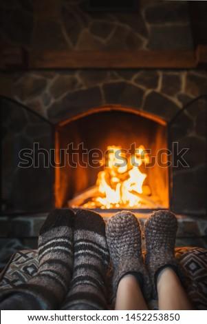 Couple in wool socks warming by cozy fire. Romantic winter #1452253850