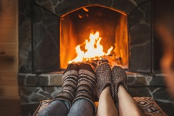 Couple in wool socks warming by cozy fire. Romantic winter eveni