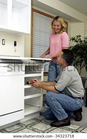 couple installing kitchen cabinet - stock photo