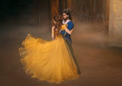 couple is dancing at fantasy ball. Happy beauty woman princess in yellow dress and guy enchanted guy, horns on head. Girl whirls in arms of male prince. Man monster costume. Silk fabric fly in motion