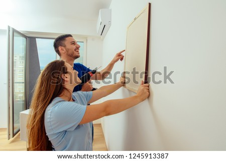 Couple is doing repair and hanging picture on the wall at home. Young family moving in