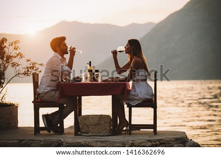 Couple is having a private event dinner on a tropical beach during sunset time