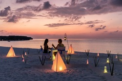 Couple is having a private event dinner on a tropical beach during sunset time: Honeymoon travel concept