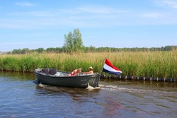 Couple is sailing at river in motor sloop boat with waving Dutch flag, Loosdrechtse Plassen, Loosdrecht, Netherlands