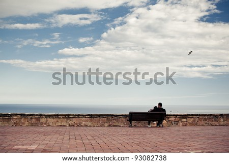 Couple is sitting on the bench and looking at the horizon, with sea and sky at the background