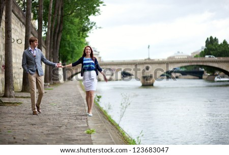 Couple is walking by the Seine embankment in Paris