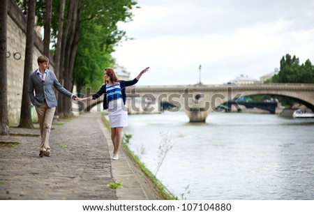Couple is walking by the Seine embankment in Paris, girl is balancing on the water edge