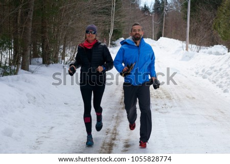 Couple, joggers, woman and man jog on a forest road at spring time.                        #1055828774