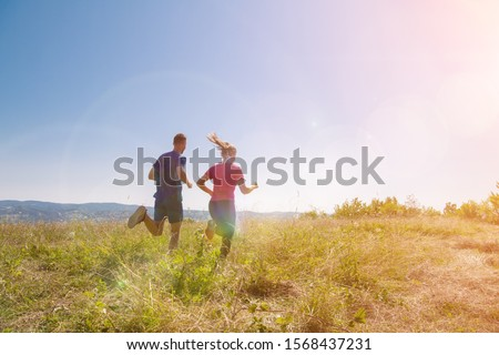 couple jogging in a healthy lifestyle on a fresh mountain air  at beautiful sunny summer nature