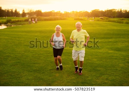 Couple jogging on grass. Senior man and woman smiling. Active leisure of pensioners. Save your health. #507823519