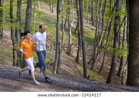 Couple jogging on gravel path beside each other with beech forest in background.