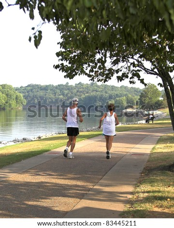Couple jogging through park along the river
