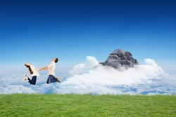 Couple jumping and holding hands against mountain peak through the clouds