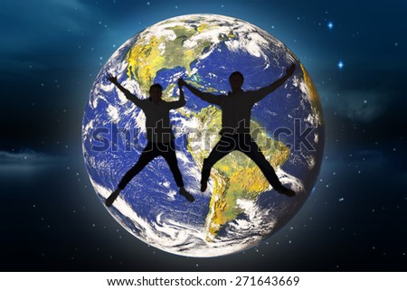 Couple jumping and holding hands against stars twinkling in night sky