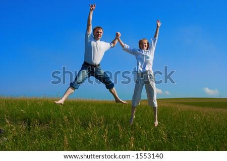 pares que saltam no campo sob o céu azul