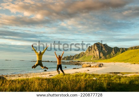 couple jumping on beach in Norway