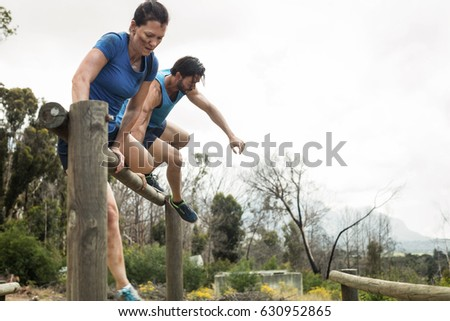 Couple jumping over the hurdles during obstacle course in boot camp Сток-фото ©
