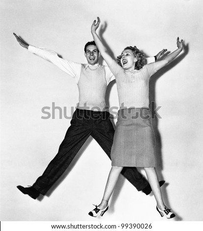 couple jumping with their arms...