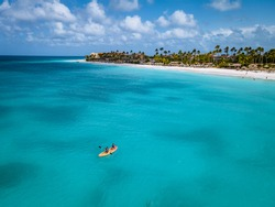 Couple Kayaking in the Ocean on Vacation Aruba Caribbean sea, man and woman mid age kayak in ocean blue clrea water white beach and palm trees Aruba