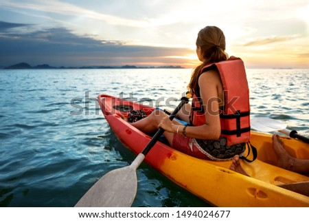 Couple kayaking together. Beautiful young couple kayaking on lake together and smiling at sunset Stok fotoğraf ©