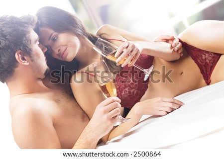 Couple kissing and drinking champagne on the bed in bedroom