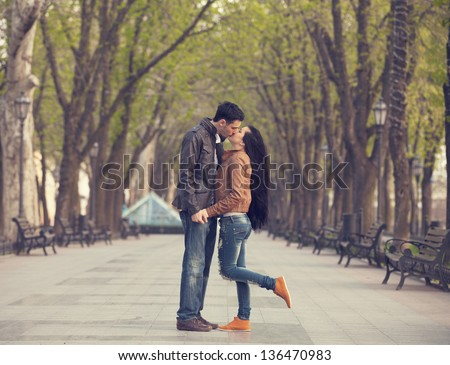 Couple kissing at alley in city.