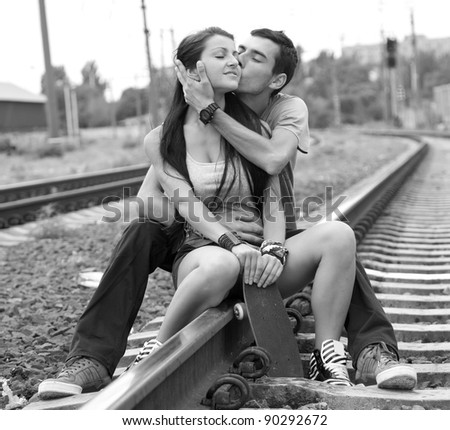 Couple kissing at railway. Photo in black and white style.