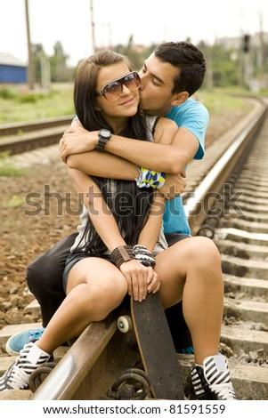 Couple kissing at railway. Urban photo.