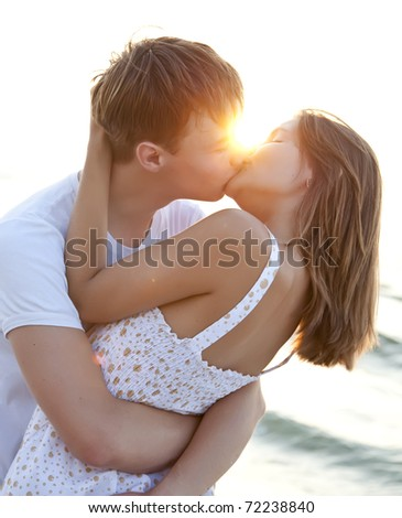 Couple kissing at sunrise - stock photo