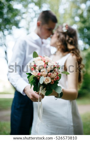 Couple kissing behind a bouquet