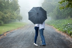 couple kissing behind the umbrella in the mist